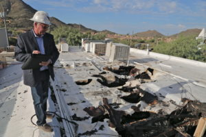 Public Insurance Adjuster on the roof of a building after a fire.
